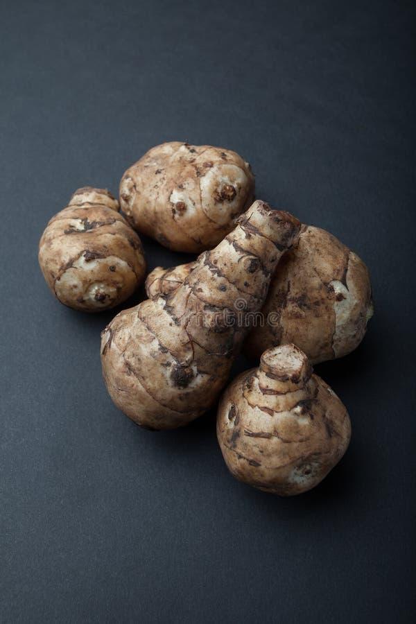 Die Knollen des organischen topinambur Topinambur auf schwarzem Hintergrund stockbilder