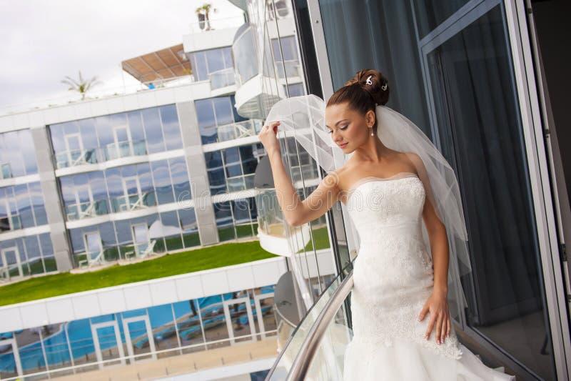 Die Kokettenbraut auf dem Balkon lizenzfreie stockfotos