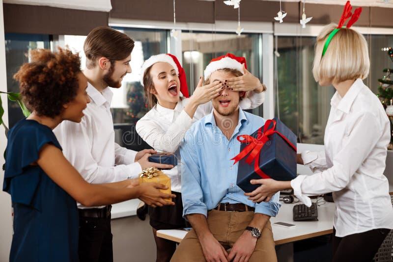 Die Kollegen, die Weihnachtsfest im lächelnden Geben des Büros feiern, stellt sich dar stockbilder