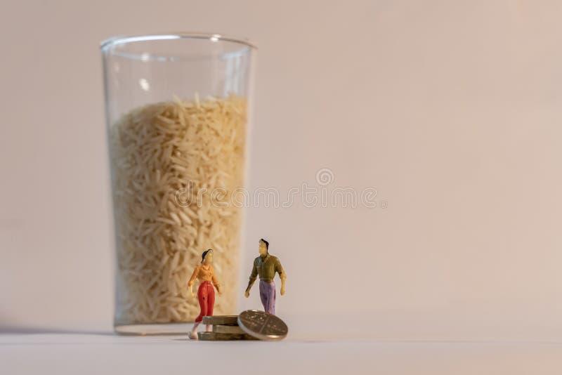 Die Kosten Aufstiegsnahrungsmitteldes steigens Frauen- und Mannzahl Stellung nahe bei großem Glas Reis und Zählungsmünzen familie lizenzfreie stockfotos