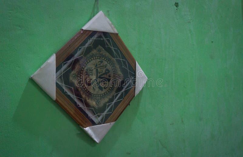 Die Kunst der Kalligraphie in einem Holz gestaltet auf grüner Wand Foto eingelassenes Jakarta Indonesien lizenzfreie stockbilder