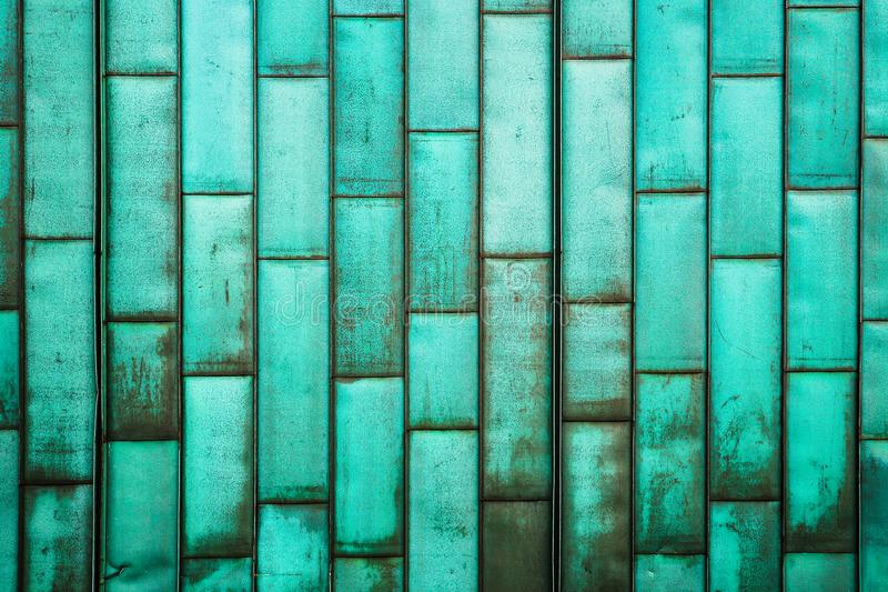 Die Kupfer-grüne Umhüllung des Gebäudes Altes Schmutzmetall deckt Wand mit Ziegeln Gebürsteter rustikaler Plattenblatt-Beschaffen stockbilder