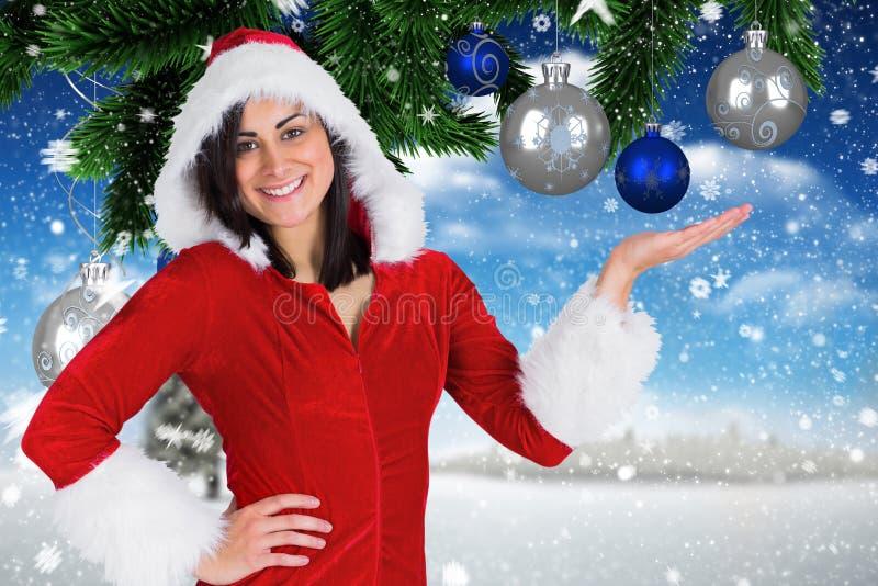 Die lächelnde Frau, die Sankt-Kostüm vortäuscht, digital zu halten trägt, erzeugte Weihnachtsflitter lizenzfreies stockfoto