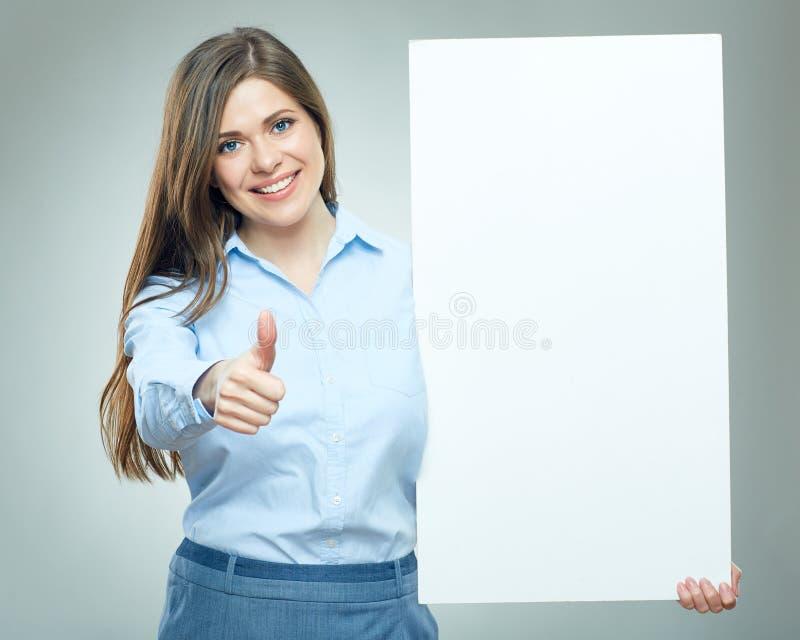 Die lächelnde Geschäftsfrau, die Daumen hält zeigt, weißes Zeichenbrett hoch stockbild