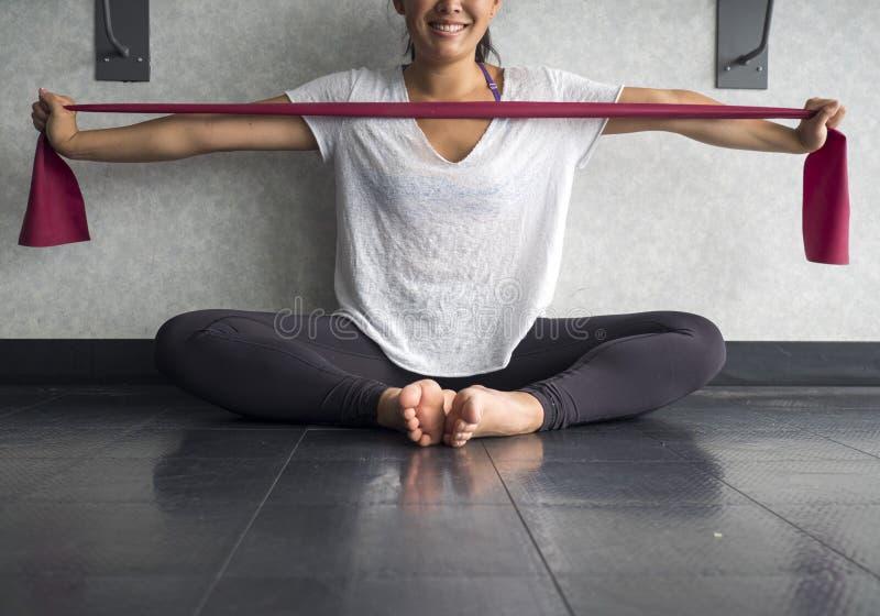Die lächelnde junge aktive Frau, die eine theraband Übung verwendet, versehen mit einem Band, um ihre Armmuskeln im Studio zu ver stockfotografie