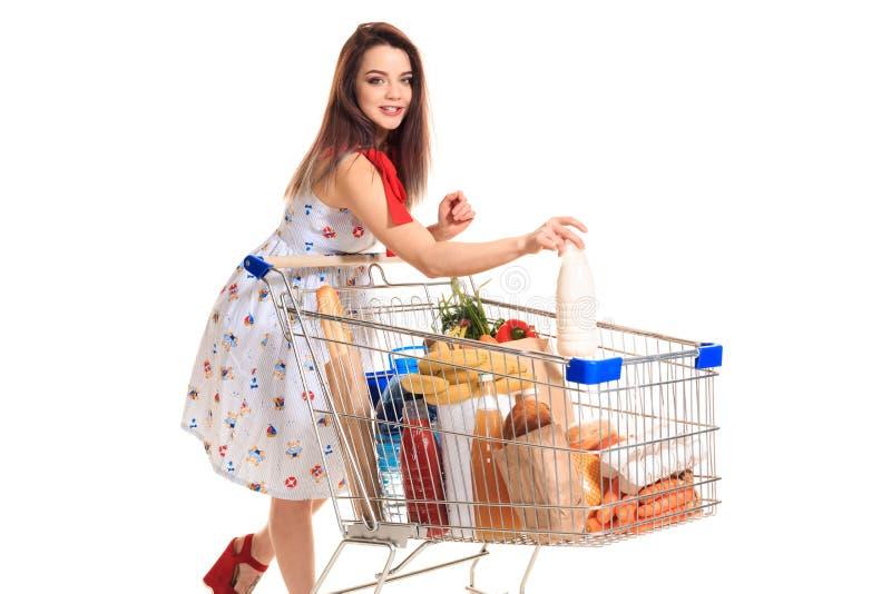 Die lächelnde junge Frau, die Einkauf am Supermarkt tut, setzt sie eine Milchflasche in den Warenkorb ein stockfoto