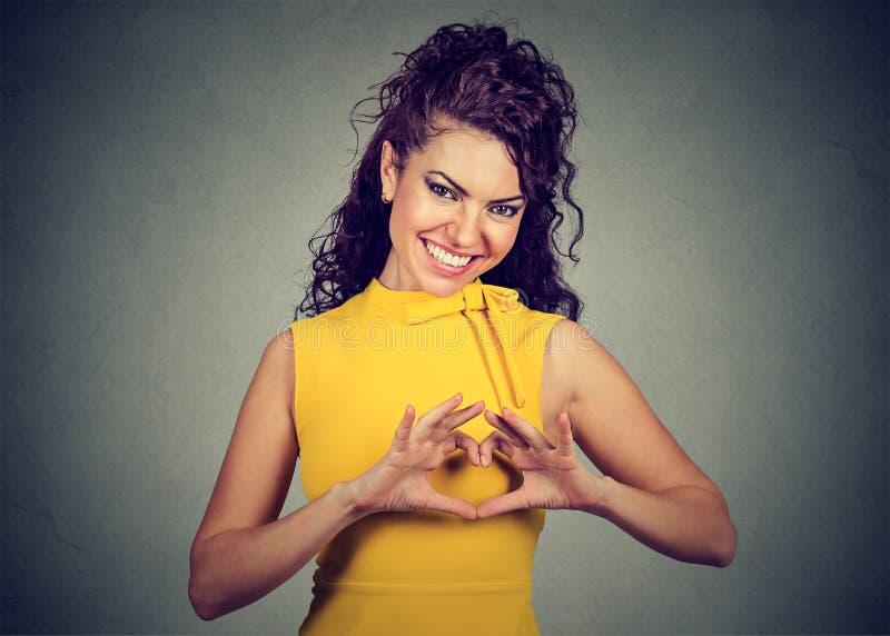 Die lächelnde nette glückliche Frau, die Herz macht, unterzeichnen mit den Händen stockfotos