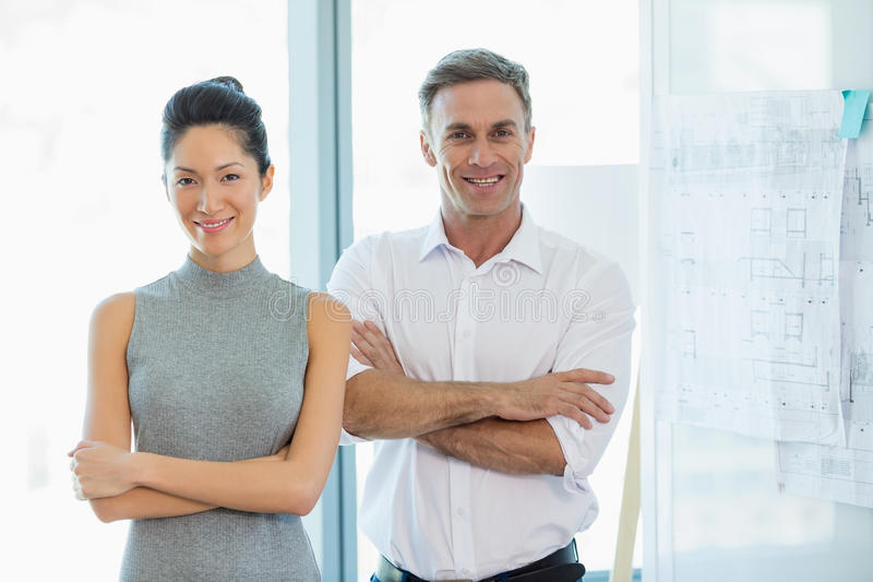 Die lächelnden Architekten, die mit den Armen stehen, kreuzten im Büro stockfotos