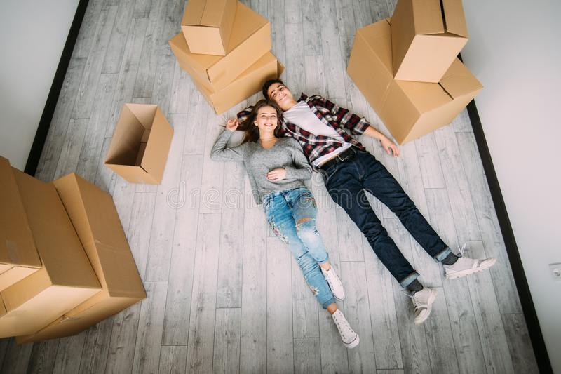 Die Lächelnpaare lagen auf dem Boden nahe Kästen, nachdem sie sich bewegt hatten Ansicht von oben lizenzfreies stockfoto