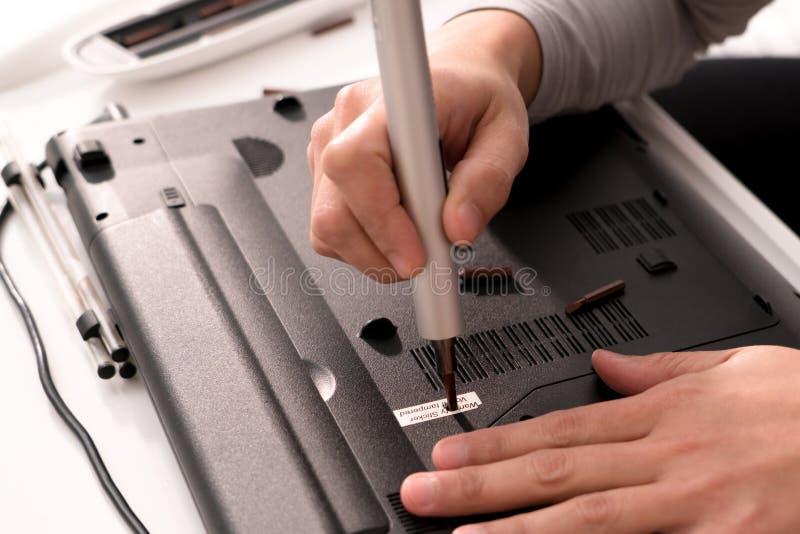 Die Lücke der Garantie nach Frauen reparieren Laptop unter Verwendung des Schraubenziehers, der Reparatur und der Wartung lizenzfreie stockfotografie
