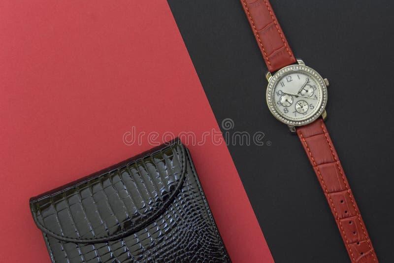 Die lackierte lederne Geldbörse der schwarzen Frauen und die Armbanduhr der Frauen auf den schwarzen und roten Hintergründen Uhr  stockfotos