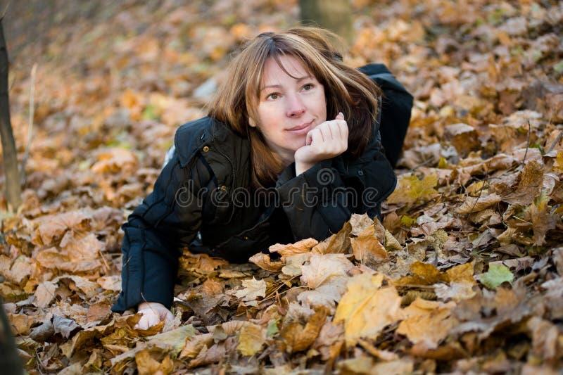 Die Lagen der jungen Frau im Herbstholz stockfotografie