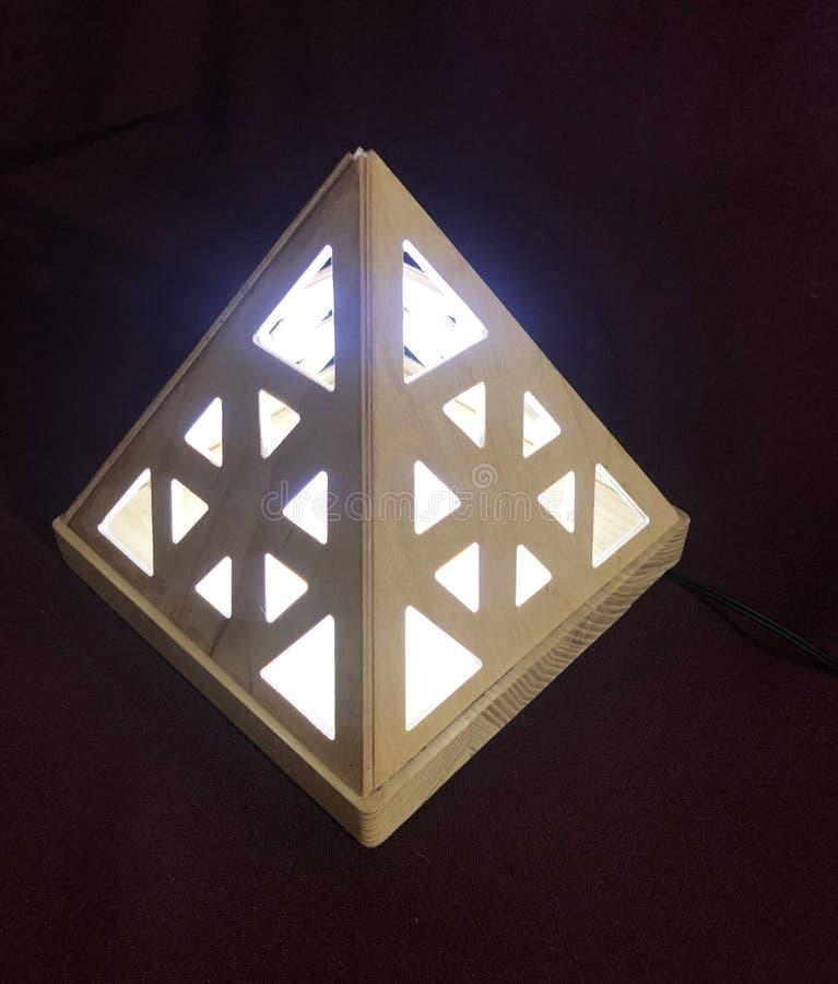 Die Lampe wird innerhalb der h?lzernen Pyramide gesetzt lizenzfreie stockfotos
