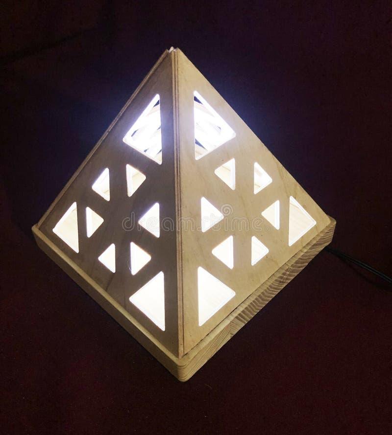 Die Lampe wird innerhalb der h?lzernen Pyramide gesetzt stockfotos