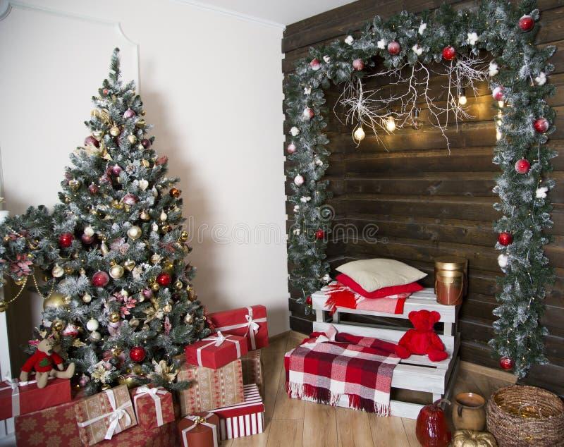 Die Landschaft des neuen Jahres zuhause Der verzierte grüne Weihnachtsbaum Es ist viele Geschenke Eine Zone mit einem Kissen und  stockfotos