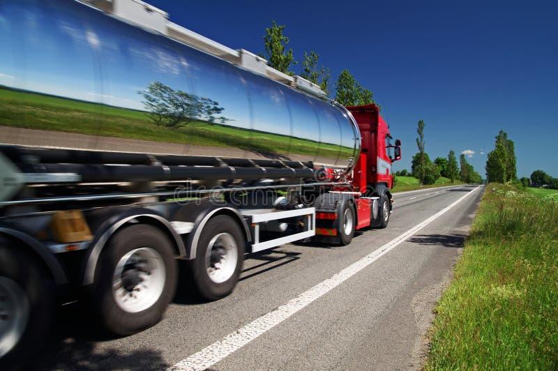 Die Landschaft widerspiegelnd, chromieren Sie den Tankwagen, der eine Landstraße weitergeht lizenzfreie stockfotos
