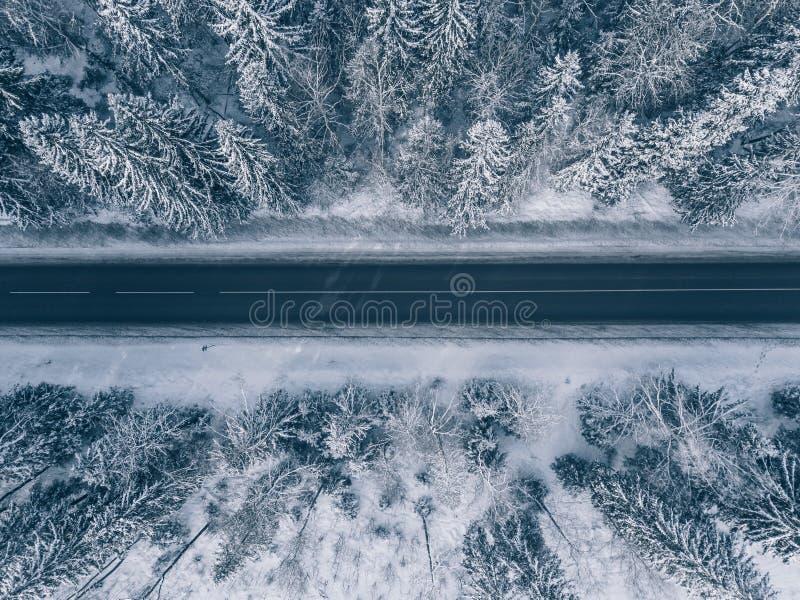 Die Landstraße, die den schönen Schnee durchläuft, umfasste Landschaften Schattenbild des kauernden Geschäftsmannes lizenzfreie stockfotografie