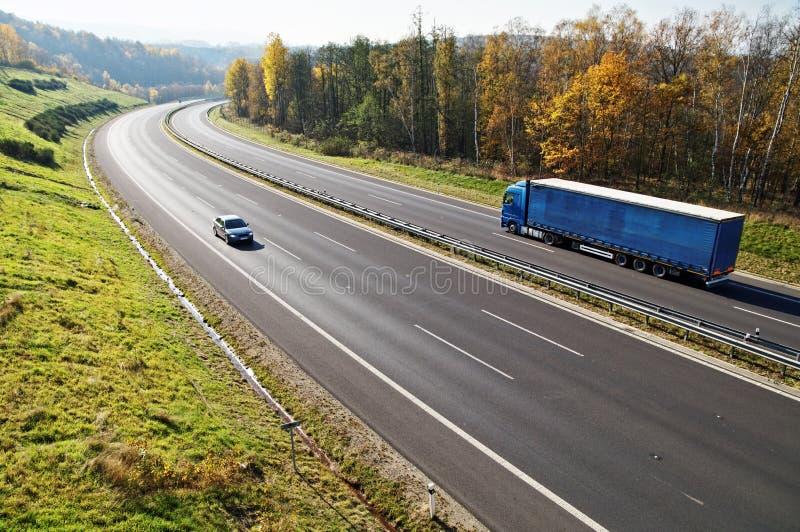 Die Landstraße zwischen Laubwäldern mit Blättern in den Fallfarben, die Landstraße geht LKW und ein Personenkraftwagen blauer stockfoto