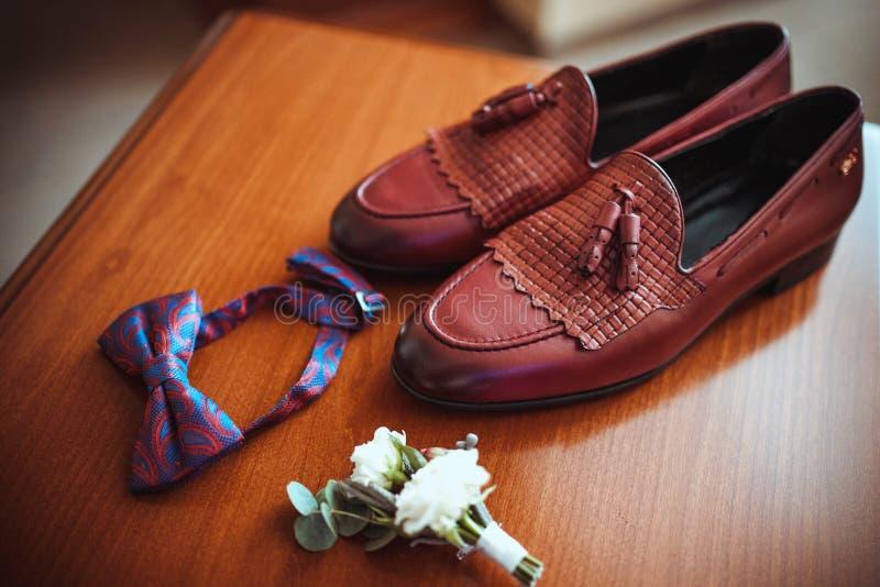 Die Lederschuhe der Männer brünieren, elegante Zusätze für den Bräutigam, Boutonniere und stilvoller Schmetterling stockfoto