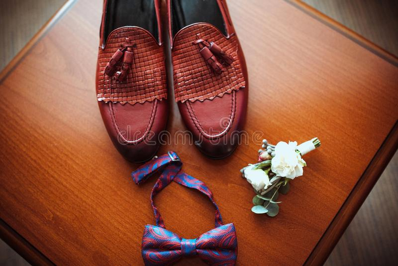 Die Lederschuhe der Männer brünieren, elegante Zusätze für den Bräutigam, Boutonniere und stilvoller Schmetterling stockfotos