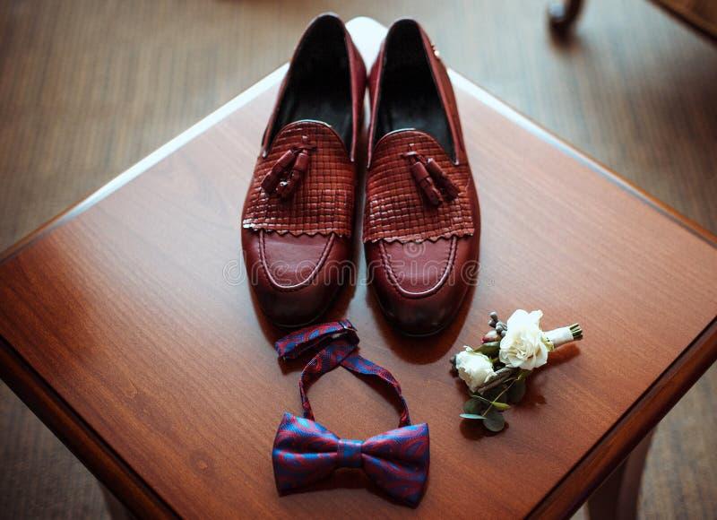Die Lederschuhe der Männer brünieren, elegante Zusätze für den Bräutigam, Boutonniere und stilvoller Schmetterling lizenzfreie stockbilder