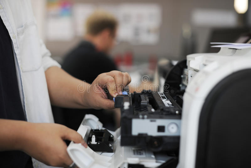 Die Leute übergeben Öffnung Drucker im Büro überprüfend stockfotos