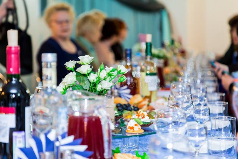 Die Leute am Bankett Ein ernstes Ereignis im Unternehmen Jahrestag oder Hochzeit Snäcke und Alkohol auf den Tabellen lizenzfreie stockbilder