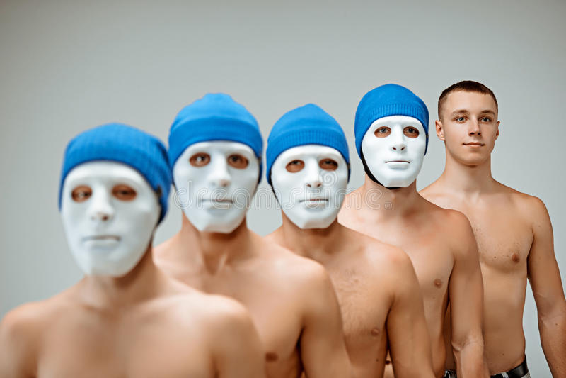 Die Leute in den Masken und ein Mann ohne Maske lizenzfreie stockfotografie