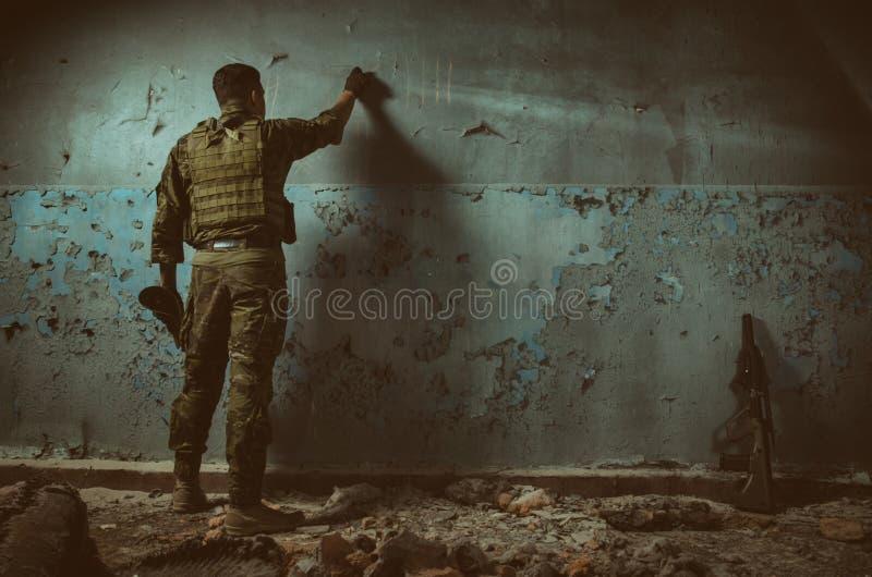 Die Leute in der Uniform mit Waffen in den Ruinen lizenzfreies stockfoto