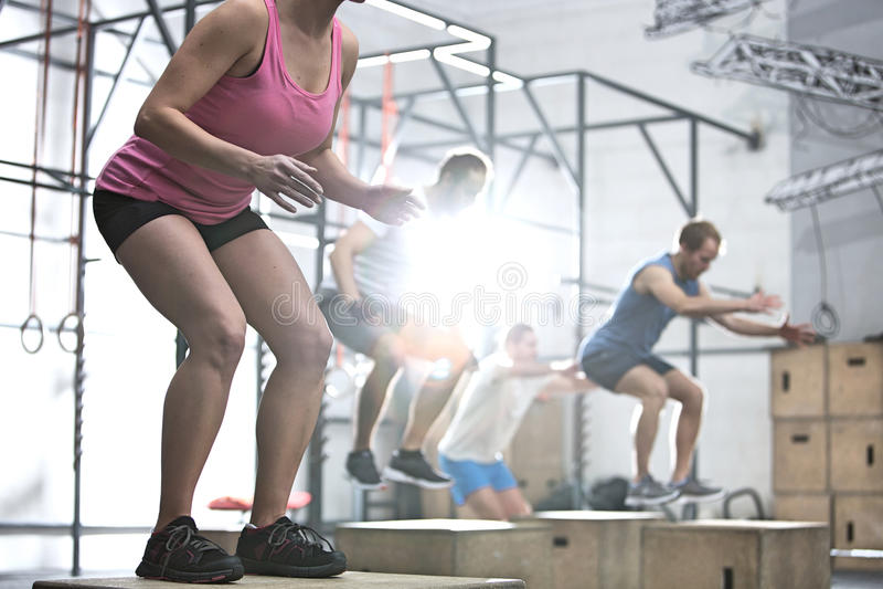 Die Leute, die Kasten tun, springen Übung in crossfit Turnhalle stockfoto
