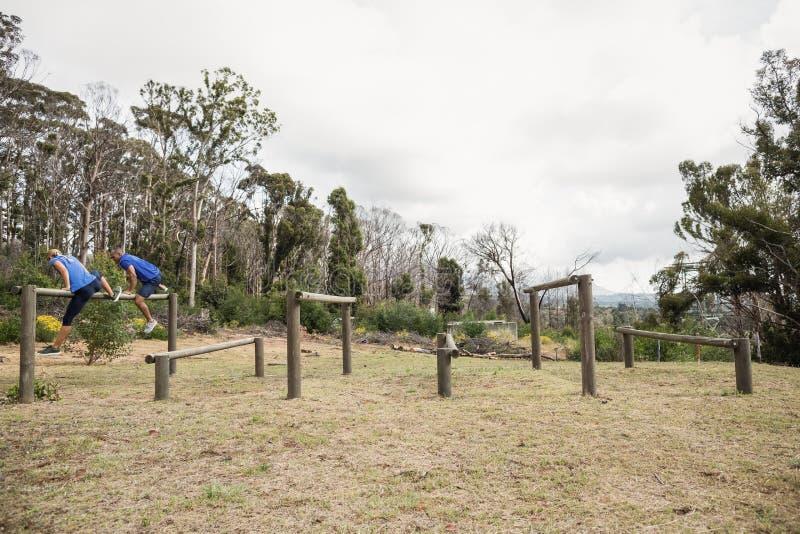 Die Leute springend über die Hürden während des Hindernislaufs stockfotografie
