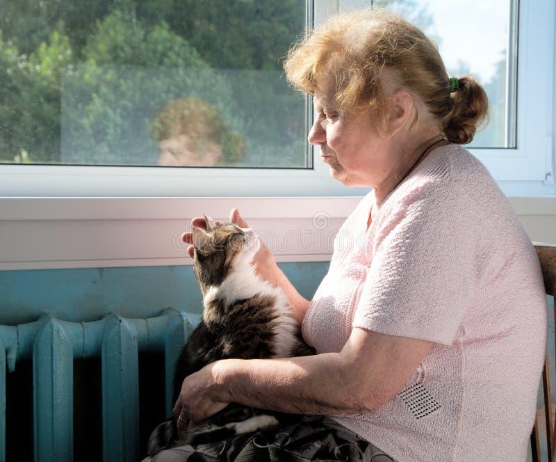 Die Liebkosungkatze der alten Frau lizenzfreies stockfoto