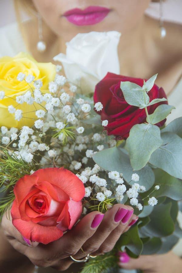 Die Lippen der Frau nahe bei einem schönen Blumenstrauß von Rosen stockfoto