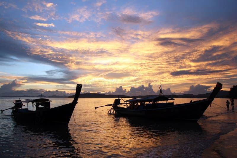 Die longtail Boote nahe zu einem Strand während eines Sonnenuntergangs stockfotografie