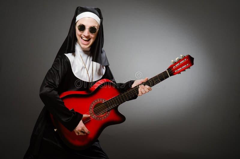 Die lustige Nonne mit dem roten Gitarrenspielen stockbilder