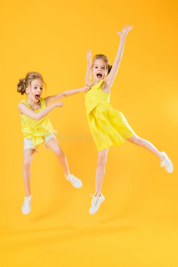 Die Mädchen der Zwillinge tanzen zusammen auf einen gelben Hintergrund stockfoto