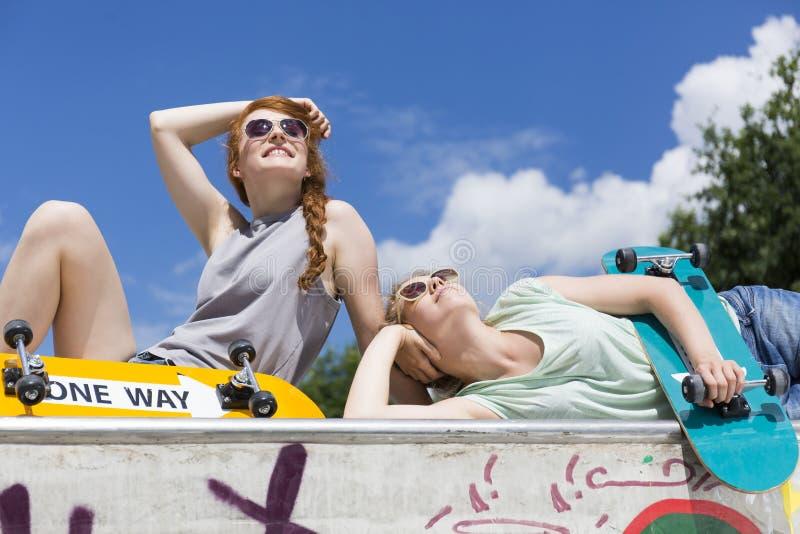Die Mädchen, die auf einem vert liegen, erhöhen mit Skateboards stockfotografie