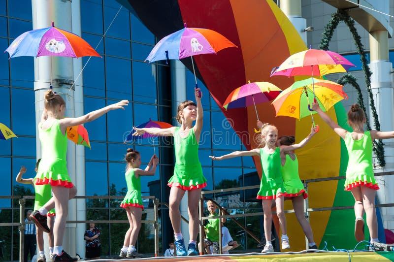 Die Mädchen führten einen Tanz mit Regenschirmen durch stockbild