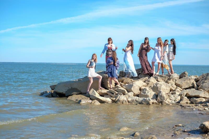 Die Mädchen ` Partei auf dem Strand Acht junge Frauen nahe dem Meer lizenzfreie stockbilder