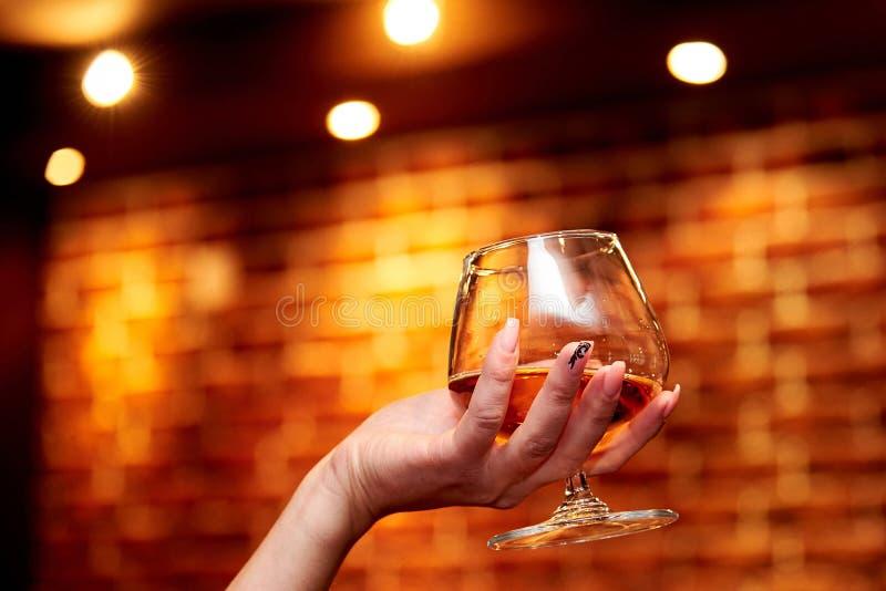 Die Mädchen ` s Hand hält ein Glas des Kognaks lizenzfreie stockfotos