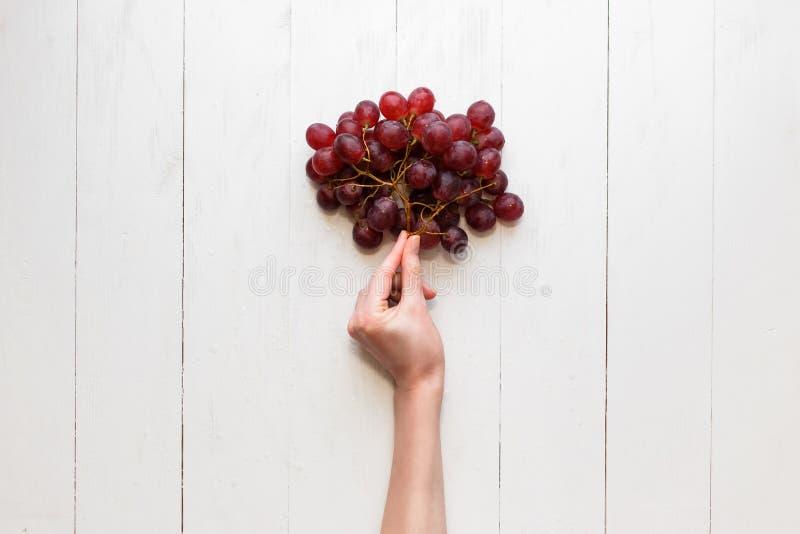 Die Mädchen ` s Hand hält an zu einem Bündel roten Trauben auf einem hölzernen Hintergrund Ansicht von oben Trauben sind wie Ball stockfotografie
