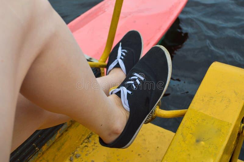 Die Mädchenfrau verdreht ihre Füße auf den Pedalen einer schwimmenden Sportanlage des Katamarans für Entspannungswege auf dem See lizenzfreie stockfotografie