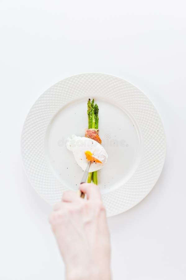 Die Mädchenhand schneidet das poschierte Ei auf dem gegrillten Spargel stockfotografie