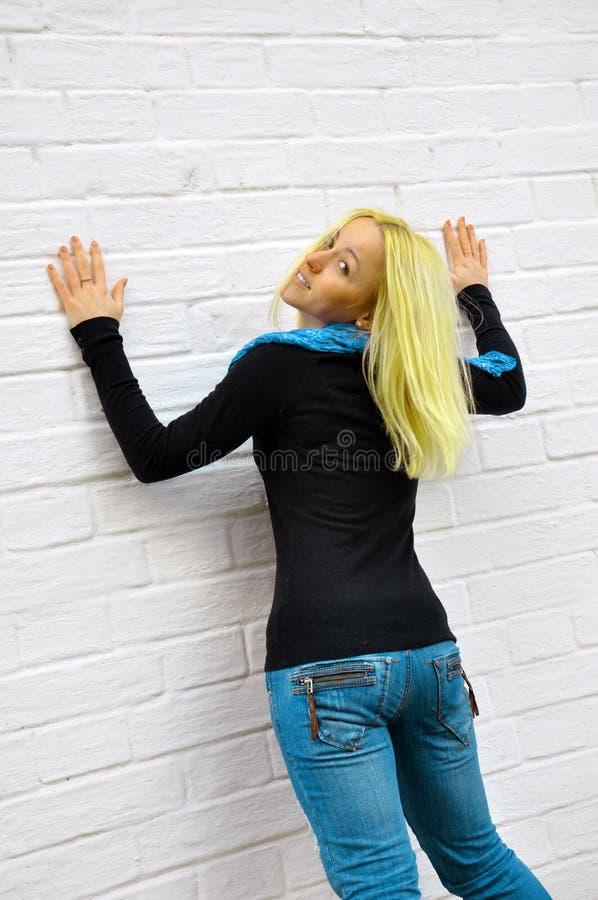 Die Mädchenkosten über eine Wand stockfotos
