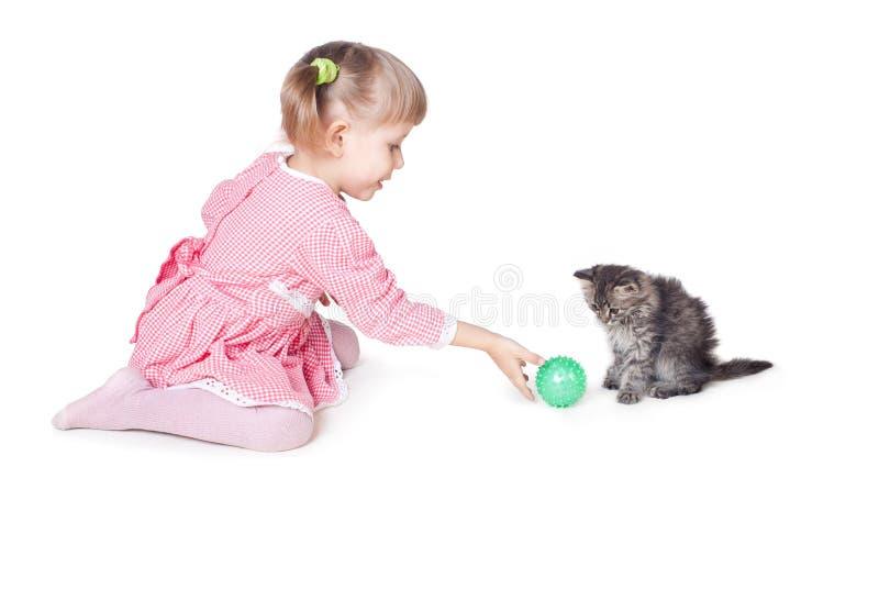Die Mädchenspiele mit einem Kätzchen lizenzfreie stockfotos