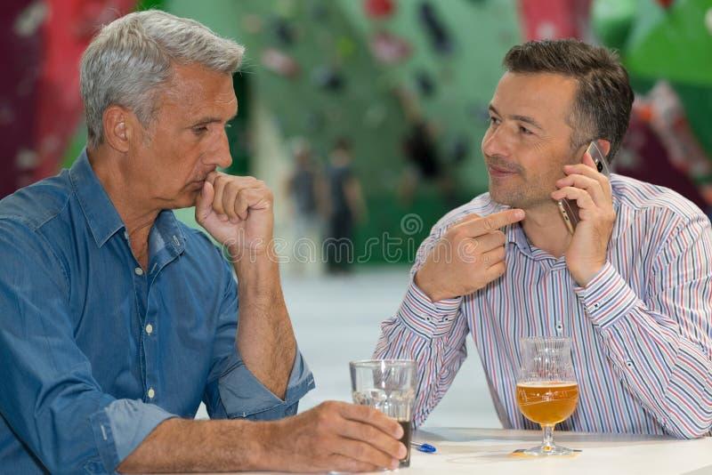 Die Männer saßen, Getränk eins habend sprechend am Telefon lizenzfreies stockfoto