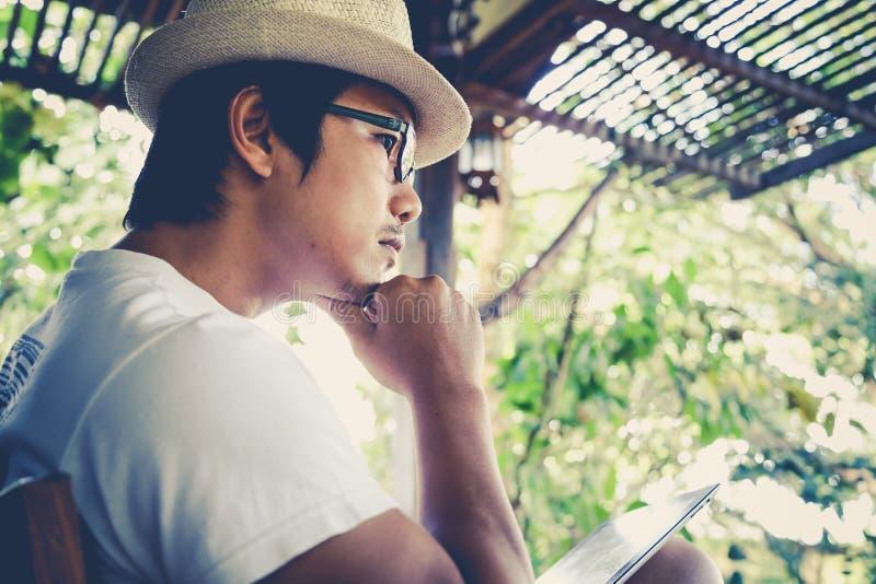 Die Männer, die unter Verwendung der Tablette sitzen, entspannen sich lizenzfreies stockfoto
