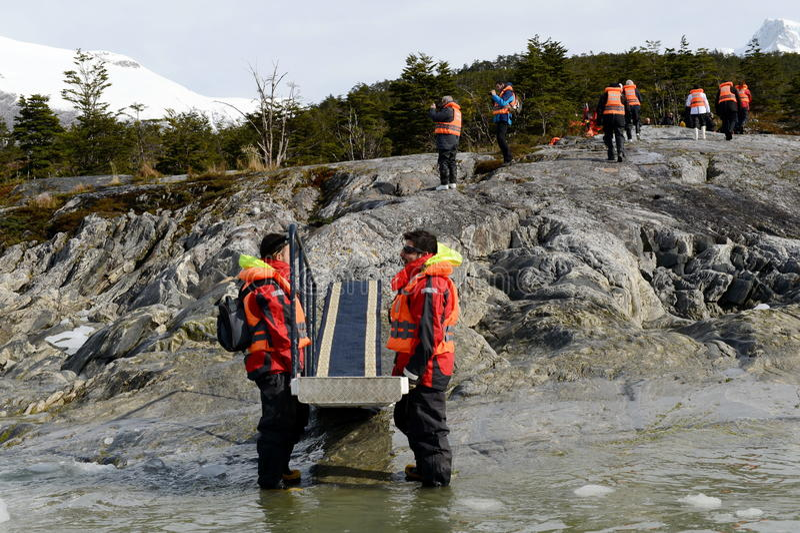 Die Männer, welche die Leiter für die Ausschiffung von Touristen vom Kreuzschiff halten - zu - Ufer nahe Pia-Gletscher stockbild