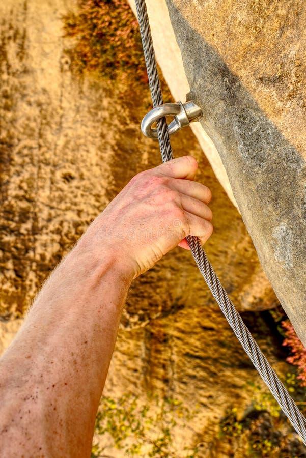 Die männliche Bergsteigerhand, die über ferrata befestigt, stellte auf Stahlkabel ein stockbild