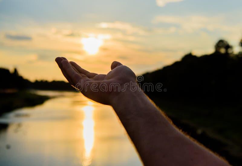 Die männliche Hand, die auf Sonne im blauen Himmel auf Abendzeit zeigt, bewundern Landschaft Gefangennahmenmoment, zum von Sonnen lizenzfreies stockbild